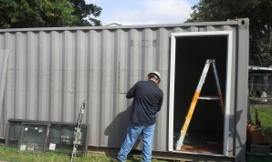 Cutting openings for one commercial 3-0 x 7-0 door and 2 windows