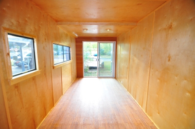 Completed interior of container with plywood wall panels and resilient flooring